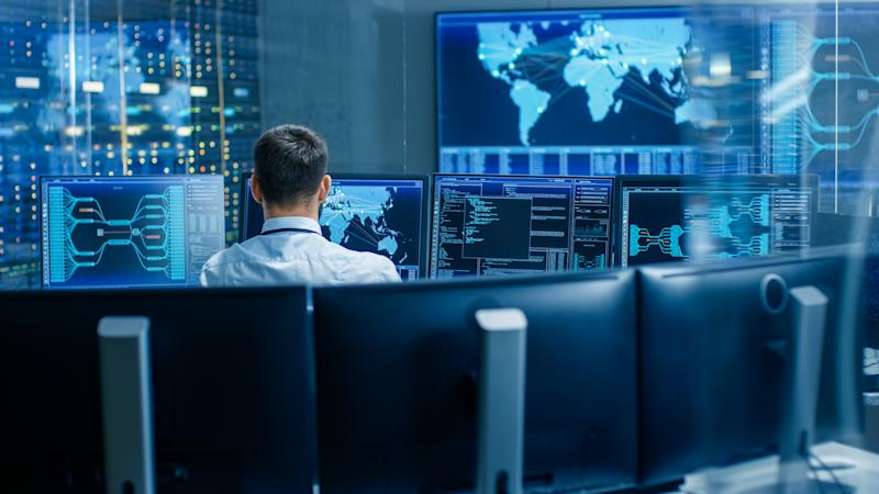 A man sitting in front of a computer surrounded by other computers in a network operations center.