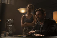 """This image released by Warner Bros. Pictures shows Thandiwe Newton, left, and Hugh Jackman in a scene from """"Reminiscence."""" (Warner Bros. Pictures via AP)"""