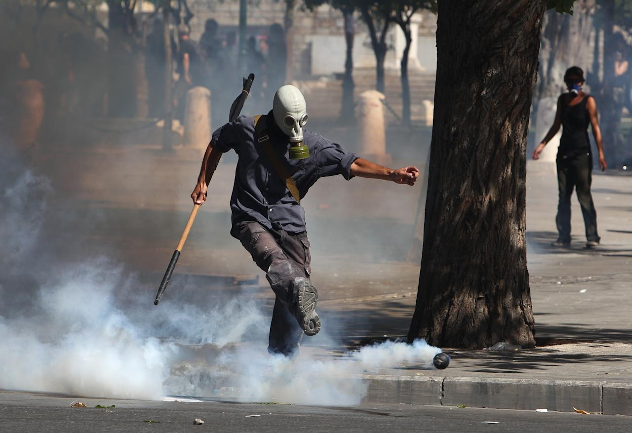 A protester kicks a tear gas canister towards riot police during a nationwide general strike in Athens, Wednesday, Sept. 26, 2012. Police clashed with protesters hurling petrol bombs and bottles in central Athens Wednesday after an anti-government rally called as part of a general strike in Greece turned violent. About 50,000 people joined the union-organized march in central Athens on Wednesday, held during a general strike against new austerity measures planned in the crisis-hit country. (AP Photo/Thanassis Stavrakis)