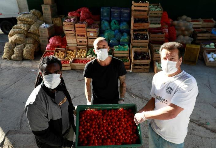 Former Brazil's head soccer coach Dunga, Internacional's soccer club player D'Alessandro and former soccer player Tinga help with food distribution to poor people, amid the coronavirus disease (COVID-19) outbreak, in Porto Alegre