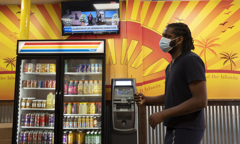 A customer waits in line at Golden Krust Caribbean restaurant, Tuesday, June 9, 2020, in Mount Vernon, N.Y. while the memorial service for George Floyd is carried on a television screen. Floyd died May 25 while in Minneapolis police custody. (AP Photo/Mark Lennihan)