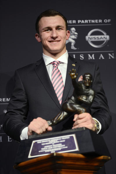 Texas A&M quarterback Johnny Manziel poses with the Heisman Trophy after becoming the first freshman to win the college football award, Saturday, Dec. 8, 2012, in New York. (AP Photo/Henny Ray Abrams)
