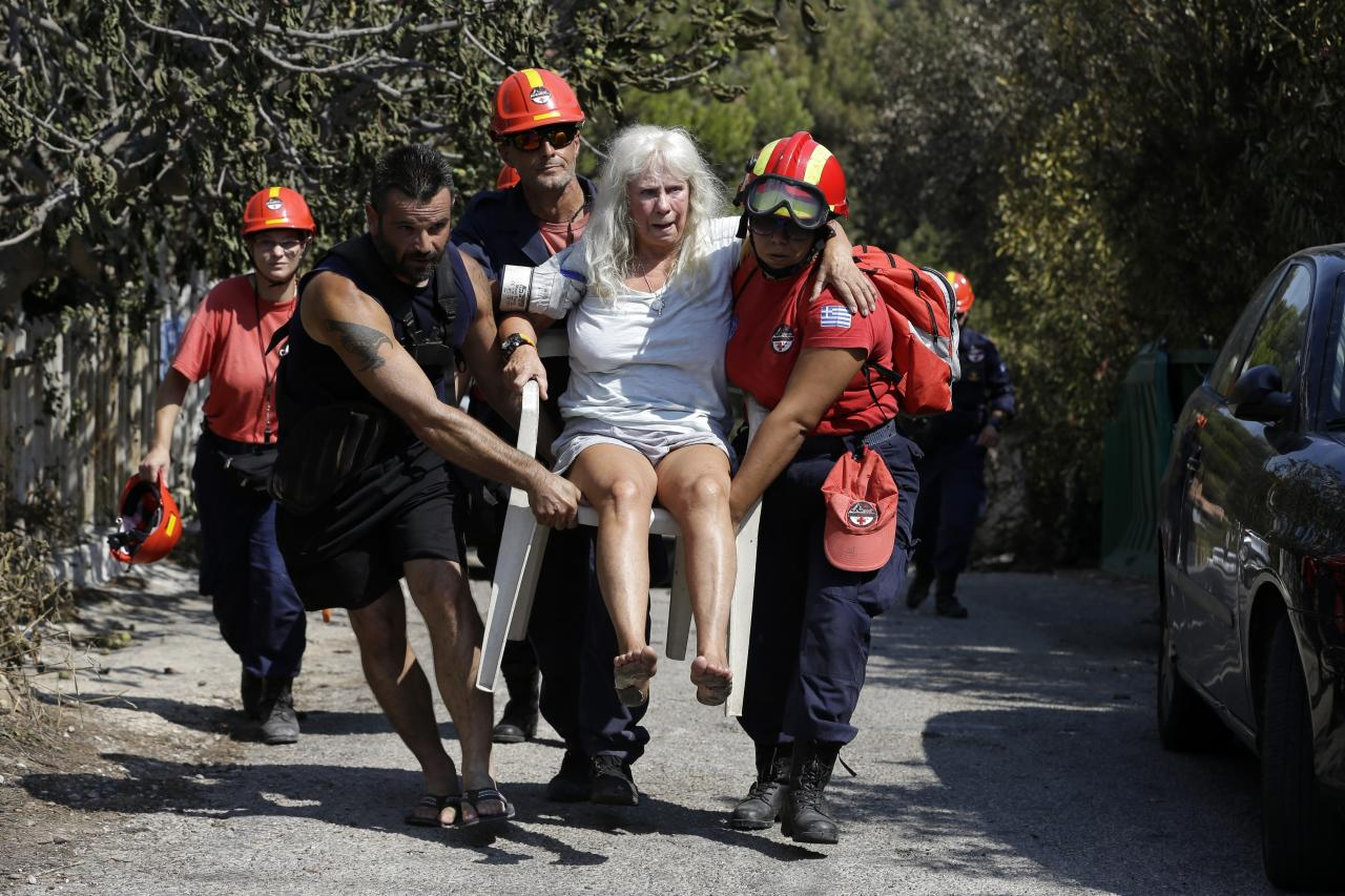 <p>Members of a rescue team carry an injured woman in Mati, east of Athens, Wednesday, July 25, 2018. (Photo: Thanassis Stavrakis/AP) </p>
