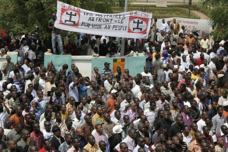 People gather in protest against the recent military coup, in Bamako, Mali Monday, March 26, 2012. About a thousand demonstrators protested Monday in Mali's capital to demand a return to constitutional order days after mutinous soldiers claimed power in a coup.(AP Photo/Harouna Traore)