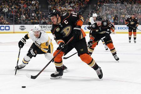Jan 11, 2019; Anaheim, CA, USA; Anaheim Ducks center Ryan Getzlaf (15) and Pittsburgh Penguins defenseman Jamie Oleksiak (6) battle for the buck in the first period at the Honda Center. Mandatory Credit: Kirby Lee-USA TODAY Sports