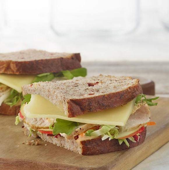 A turkey, apple, and cheddar sandwich from Panera, displayed on a wood cutting board.