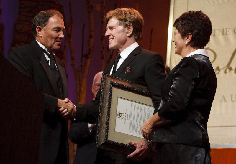 Gov. Gary Herbert and his wife Jeanette present Robert Redford with the declaration that Nov. 9, 2013 is Robert Redford Day. For all his contributions to the state of Utah, Robert Redford was recognized and honored by Governor Gary Herbert at a gala in his honor at the Grand America Hotel, Saturday, Nov. 9, 2013. (AP Photo/The Salt Lake Tribune, Leah Hogsten)