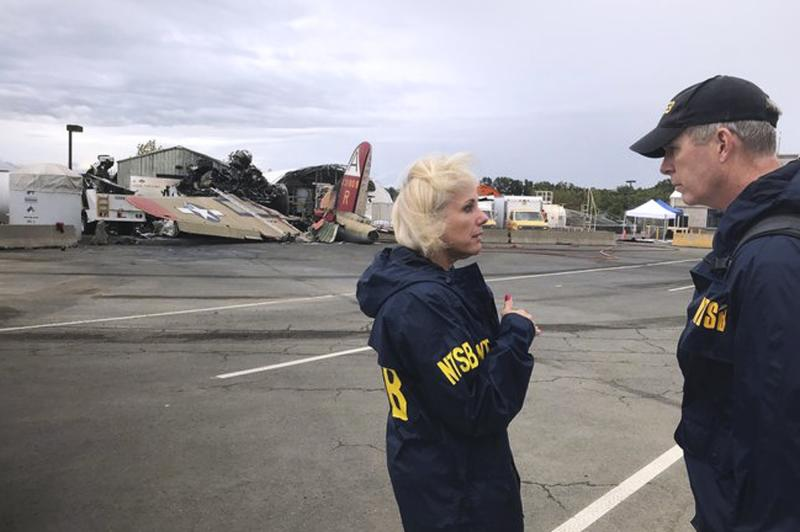 In this photo released via Twitter by the National Transportation Safety Board, NTSB board Member Jennifer Homendy, left, and investigator Dan Bower stand at the scene where a World War II-era bomber plane, left, crashed at Bradley International Airport in Windsor Locks, Conn., Wednesday, Oct. 2, 2019. (National Transportation Safety Board via AP)