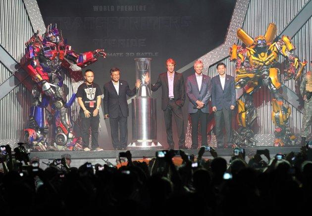 "As winner of the USS ""Pledge your Allegiance"" competition, Malcolm Chen had the privilege of standing on stage to launch the Transformers ride by activating the Allspark with Michael Bay and other VIPs. (Photo courtesy of RWS)"