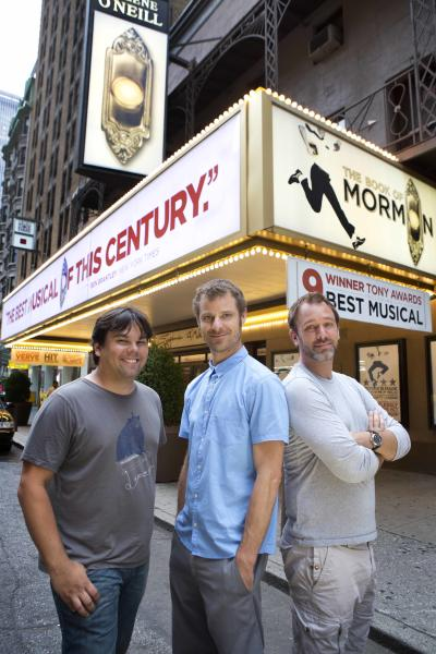 "This July 2012 image released by Boneau/Bryan-Brown shows, from left, Robert Lopez, Matt Stone and Trey Parker are shown in front of the Eugene O'Neill theater where the Tony-award winning musical ""The Book of Mormon,"" is performing in New York. The nine-time Tony Award-winning musical opens its first national tour in Denver this month. (AP Photo/Boneau/Bryan-Brown, Joan Marcus)"