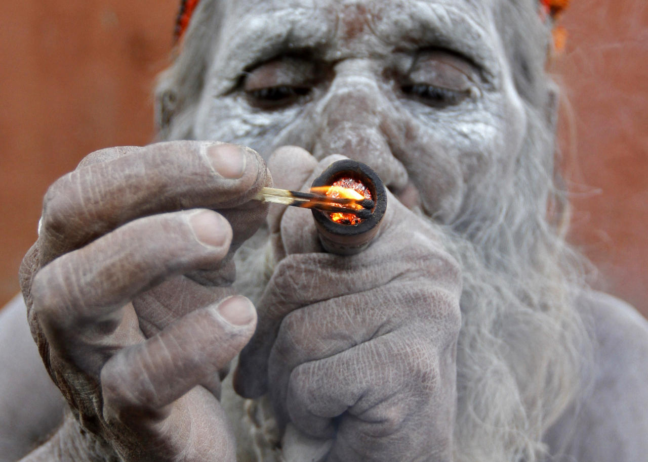 A Hindu ascetic smokes marijuana outside the Bhavnath temple during the Mahashivratri festival in Gujarat.