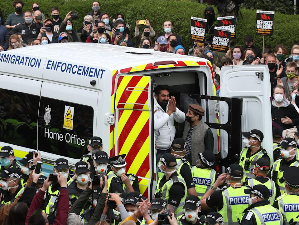 <p>One of the two detained men thanks crowds as he is freed from the immigration van in Kenmure Street, Glasgow, on Thursday</p> (PA)
