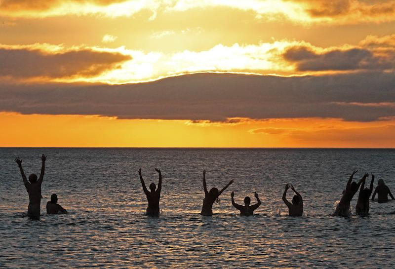 File photo for illustration shows nudists taking part in the annual North East Skinny Dip as the sun rises at Druridge Bay in Northumberland, northeast England on September 22, 2013