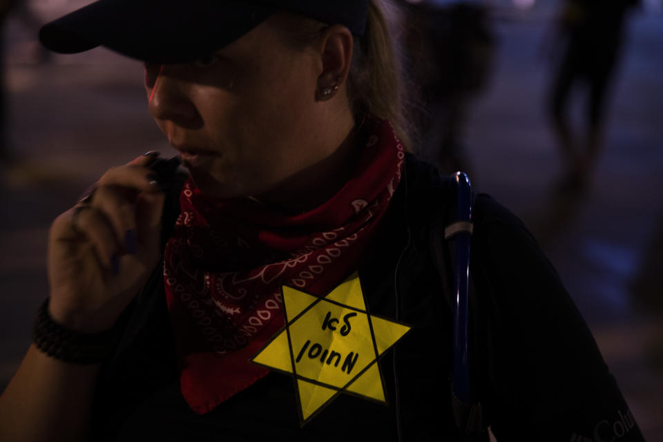 """A woman wears a yellow Star of David, like the ones Jews were obligated to wear during World War II, with Hebrew reads """"not vaccinated"""" during a protest against the Health Ministry's """"green pass"""" system, in Tel Aviv, Israel, Saturday, Oct. 2, 2021. Israel restricted its coronavirus """"green pass"""" on Sunday to those who have received a COVID-19 booster or recently recovered, sparking protests by opponents who say the system is a form of forced vaccination. (AP Photo/Oded Balilty)"""