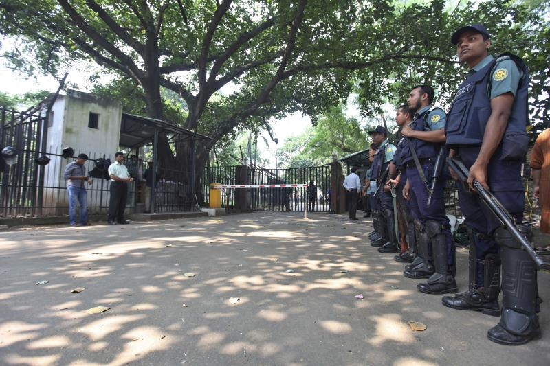 Bangladeshi policemen stand guard outside the special war crimes tribunal in Dhaka, Bangladesh, Sunday, Nov. 3, 2013. The tribunal on Sunday sentenced to death two Bangladeshis now living in the U.S. and Britain for crimes against humanity during the country's independence war against Pakistan in 1971. (AP Photo/Suvra Kanti Das)