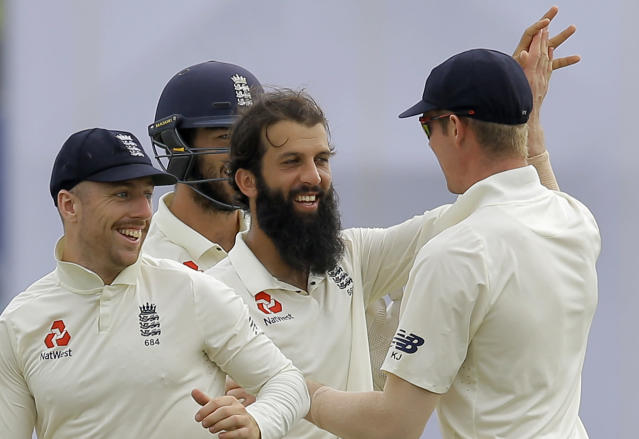 England's Moeen Ali, center, celebrates the dismissal of Sri Lanka's Niroshan Dickwella with team mates during the fourth day of the first test cricket match between Sri Lanka and England in Galle, Sri Lanka, Friday, Nov. 9, 2018. (AP Photo/Eranga Jayawardena)