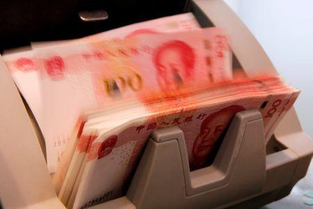 Chinese 100 yuan banknotes are seen in a counting machine while a clerk counts them at a branch of a commercial bank in Beijing