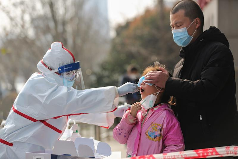 A medical staff member (L) collects sample from a girl for a nucleic acid test for the COVID-19 coronavirus at a residental area in Wuhan in China's central Hubei province on March 5, 2020. - China on March 5 reported 31 more deaths from the COVID-19 coronavirus epidemic, taking the country's overall toll past 3,000, with the number of new infections slightly increasing. (Photo by STR / AFP) / China OUT (Photo by STR/AFP via Getty Images)