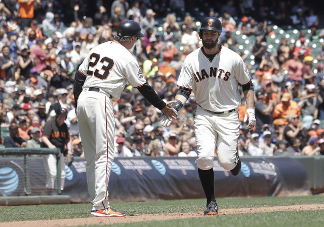 San Francisco Giants' Brandon Belt, right, is congratulated by third base coach Ron Wotus (23) after hitting a home run against the Cincinnati Reds in the third inning of a baseball game in San Francisco, Wednesday, May 16, 2018. (AP Photo/Jeff Chiu)