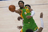 Utah Jazz guard Donovan Mitchell (45) goes to the basket as Houston Rockets guard Kevin Porter Jr., foreground, defends during the first half of an NBA basketball game Friday, March 12, 2021, in Salt Lake City. (AP Photo/Rick Bowmer)