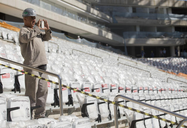 A worker takes a picture at the Itaquerao, the stadium that will host the World Cup opener in less than three months in Sao Paulo, Brazil, Saturday, March 15, 2014. The Itaquerao was one of the six stadiums that were supposed to be finished by the end of 2013, but a crane collapse that killed two workers in November caused significant delays to the venue where Brazil will play Croatia on June 12. The stadium is not expected to be ready before mid-April. (AP Photo/Andre Penner)