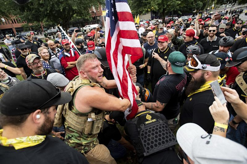Proud Boys demonstrators in tactical vests plant a U.S. flag in a park
