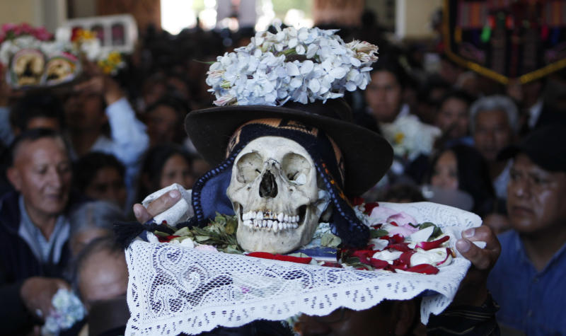 "A man carries a decorated human skull or ""natita"" inside the Cementerio General chapel during the Natitas Festival celebrations in La Paz, Bolivia, Friday, Nov. 8, 2013. The Roman Catholic church considers the skull festival to be pagan, but it doesn't prohibit people from participating in it. Mass was not being held at the chapel on Friday, but a bowl of holy water was left out so people could bless the skulls they were carrying in the ritual celebrated a week after Day of the Dead. (AP Photo/Juan Karita)"