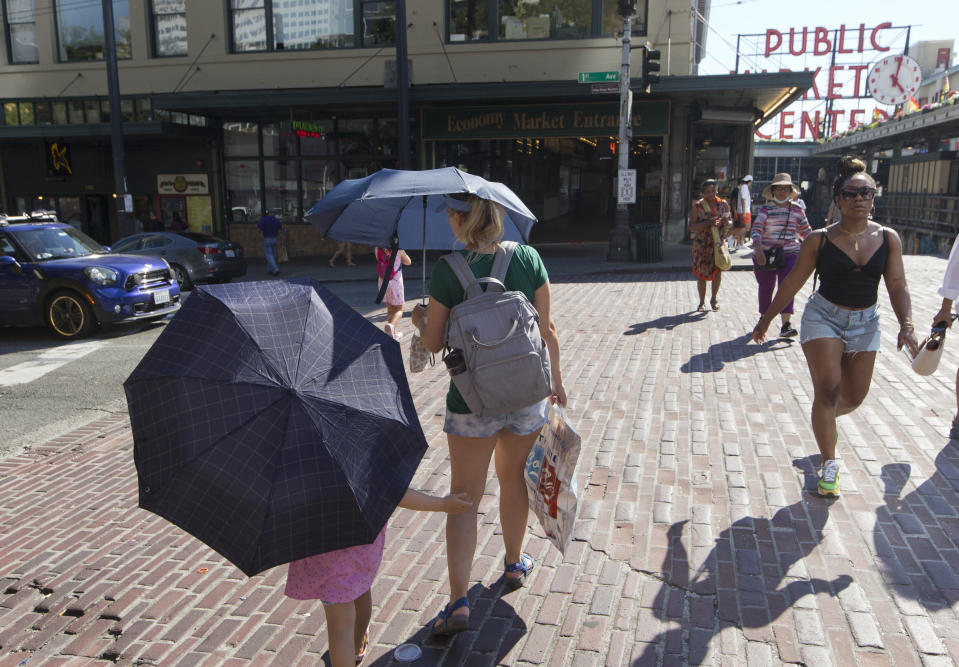 Sabina Ehmann and her daughter Vivian, visiting Seattle from North Carolina, are prepared with umbrellas to shield the sun during a heat wave hitting the Pacific Northwest, Sunday, June 27, 2021, in Seattle. Yesterday set a record high for the day with more record highs expected today and Monday. (AP Photo/John Froschauer)