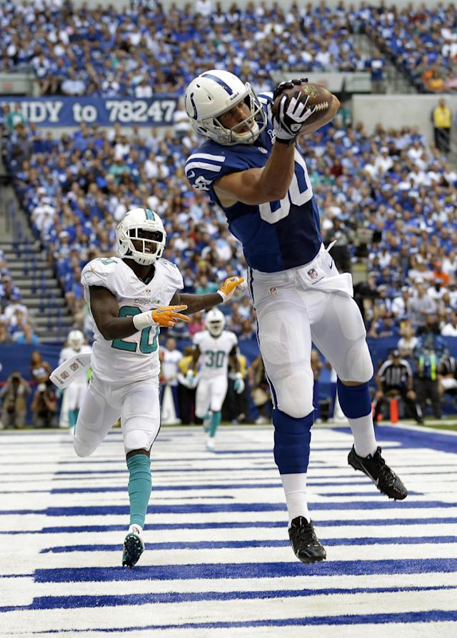 Indianapolis Colts' Coby Fleener (80) makes a 3-yard touchdown reception against Miami Dolphins' Reshad Jones (20) during the first half an NFL football game Sunday, Sept. 15, 2013, in Indianapolis. (AP Photo/Michael Conroy)