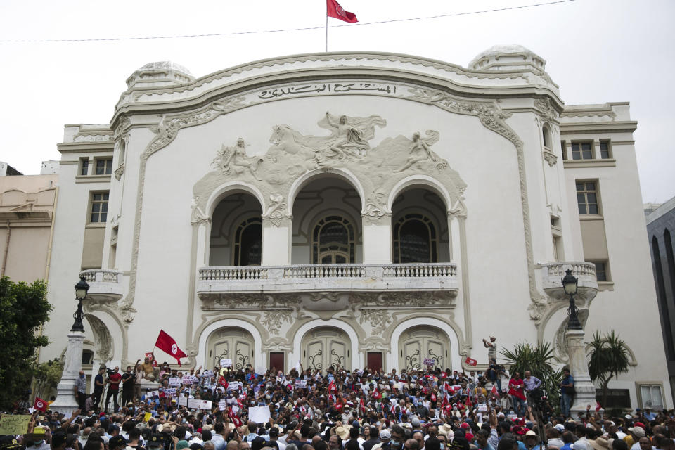 Tunisian demonstrators gather outside the Municipal Theatre of Tunis during a protest against Tunisian President Kais Saied, Saturday, Sept. 18, 2021. In July Tunisian President Kais Saied fired the country's prime minister and froze parliament's activities after violent demonstrations over the country's pandemic and economic situation. The movement made by Saied was considered by his opponents as a coup. (AP Photo/Riadh Dridi)