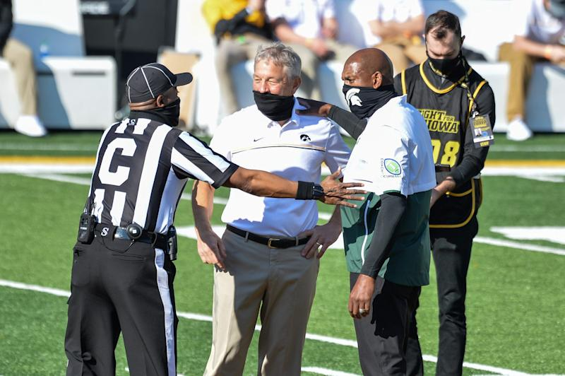 Iowa coach Kirk Ferentz (center) and Michigan State coach Mel Tucker (right) talk with an official before the game on Saturday, Nov. 7, 2020, in Iowa City, Iowa.