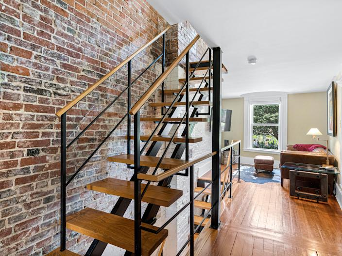A brick wall and staircase on the left side of a room with wood floors and a window in the back