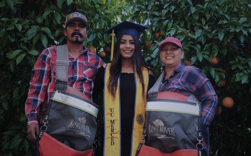 Anna Ocegueda, who will graduate from college on Sunday, poses with her migrant parents. (Photo: Twitter)
