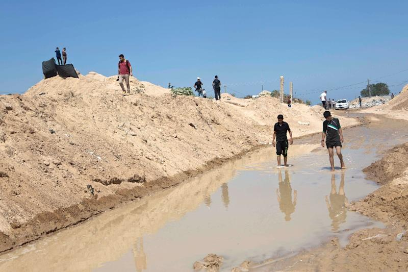 Palestinians stand in a pool of water next to the entrance of tunnels, used for smuggling supplies between Egypt and the Gaza Strip, on September 18, 2015 in Rafah, in southern Gaza (AFP Photo/Said Khatib)