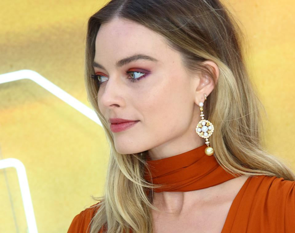 Margot Robbie matched her makeup to her sunset-hued gown [Photo via PA]