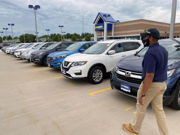 """Brandon Parrum, general manager of CarMax's Des Moines store, walks past vehicles that customers can arrange to buy online and collect at the store using """"contactless"""" curbside pickup"""