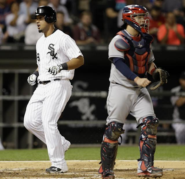 Chicago White Sox's Jose Abreu, left, scores on a double hit by Adam Dunn as Cleveland Indians catcher Roberto Perez looks to the field during the third inning of a baseball game in Chicago, Wednesday, Aug. 27, 2014. (AP Photo/Nam Y. Huh)