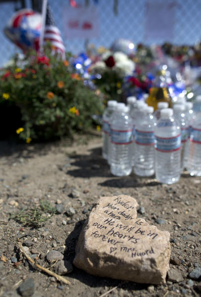 A note written on a rock for the son of firefighter Andrew Ashcraft sits at a memorial outside the Granite Mountain Interagency Hotshot Crew fire station, Tuesday, July 2, 2013 in Prescott, Ariz. Ashcraft was one of 19 firefighters killed by an out-of-control blaze, Sunday, near Yarnell, Ariz. (AP Photo/Julie Jacobson)