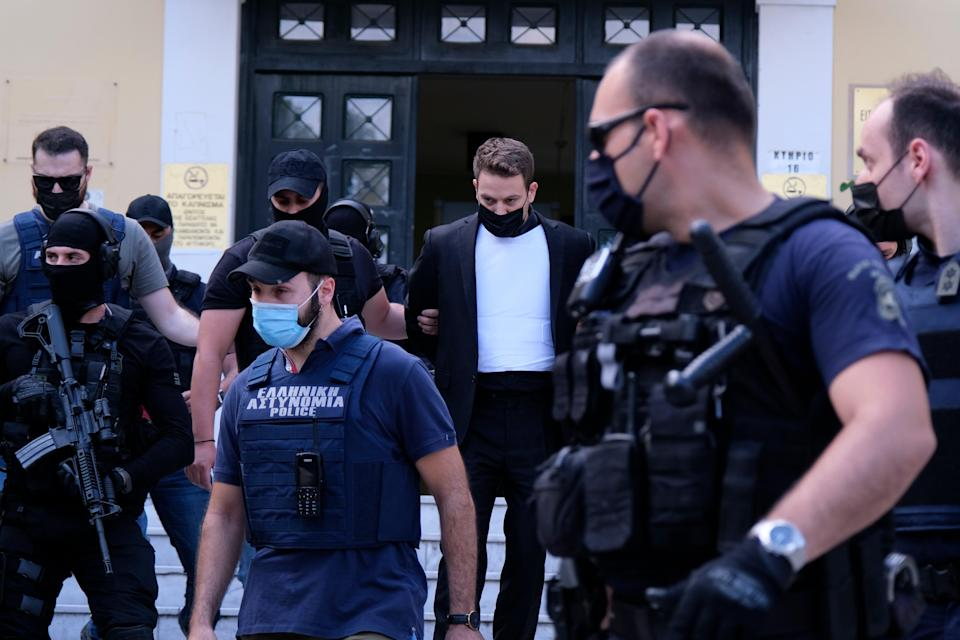 Babis Anagnostopoulos, escorted by police, leaves the court in Athens (AP)
