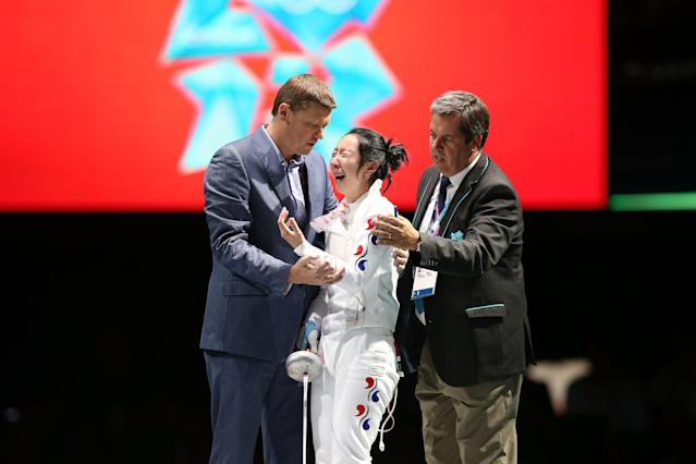 LONDON, ENGLAND - JULY 30: A Lam Shin of Korea gets escorted off stage after a faulty clock ended her match against Britta Heidemann of Germany in the Women's Epee Individual Fencing Semifinals on Day 3 of the London 2012 Olympic Games at ExCeL on July 30, 2012 in London, England. Heidemann scored the final point with one second left on the clock to win against Shin. (Photo by Ezra Shaw/Getty Images)