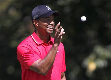 Tiger Woods catches a ball before his putt from his caddie on the second hole at the Tour Championship golf tournament in Atlanta