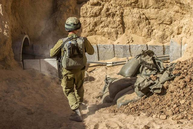 An Israeli army officer stands at the entrance of a tunnel said to be used by Palestinian militants for cross-border attacks, during an army organised tour for journalists on July 25, 2014. U.S. Secretary of State John Kerry pressed regional leaders to nail down a Gaza ceasefire on Friday as the civilian death toll soared, and further violence flared between Israelis and Palestinians in the occupied West Bank and Jerusalem. REUTERS/Jack Guez/Pool (POLITICS CIVIL UNREST CONFLICT)