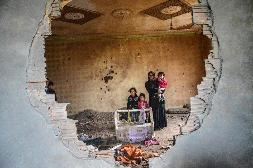 A women and her children stand in the ruins of battle-damaged house in the Kurdish town of Silopi, in southeastern Turkey, near the border with Iraq on January 19, 2016 (AFP Photo/Ilyas Akengin)