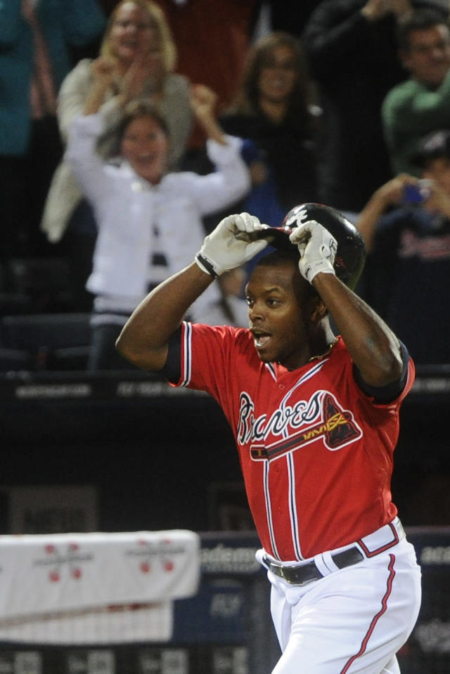 Atlanta Braves' Justin Upton celebrates as he makes his way down the third base line to home on his game-winning walk off home run against the Washington Nationals during the 10th inning of a baseball game in Atlanta, Friday, Aug. 16, 2013. Atlanta won 3-2 in 10 innings. (AP Photo/John Amis)