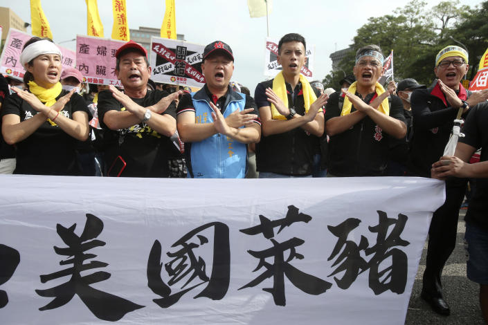 """People shout slogans with a banner reading """"U.S. ractopamine pork"""" during a protest in Taipei, Taiwan, Sunday, Nov. 22. 2020. Thousands of people marched in streets on Sunday demanding the reversal of a decision to allow U.S. pork imports into Taiwan, alleging food safety issues. (AP Photo/Chiang Ying-ying)"""