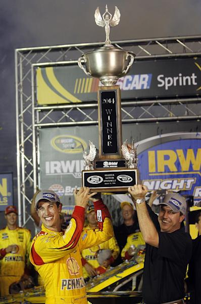 Joey Logano hoists the trophy with Jerry Caldwell, General Manager of Bristol Motor Speedway after winning a NASCAR Sprint Cup Series auto race at Bristol Motor Speedway on Saturday, Aug. 23, 2014, in Bristol, Tenn. (AP Photo/Wade Payne)