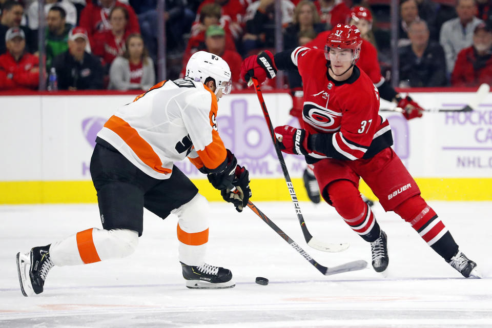 Carolina Hurricanes' Andrei Svechnikov (37), of Russia, works the puck as Philadelphia Flyers' Ivan Provorov (9), of Russia, defends during the second period of an NHL hockey game in Raleigh, N.C., Thursday, Nov. 21, 2019. (AP Photo/Karl B DeBlaker)