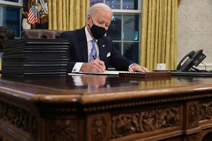 Joe Biden signs a slate of 17 executive actions hours after taking office. (Getty Images)