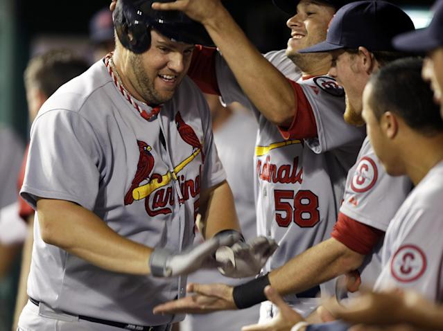 CORRECTS DATE TO WEDNESDAY, SEPT. 4, NOT EARLY THURSDAY SEPT. 5- St. Louis Cardinals' Matt Adams, left, is congratulated in the dugout after hitting a solo home run in the 16th inning of a baseball game against the Cincinnati Reds, Wednesday, Sept. 4, 2013, in Cincinnati. Adams hit two home runs in the game won by St. Louis 5-4 in 16 innings. (AP Photo/Al Behrman)