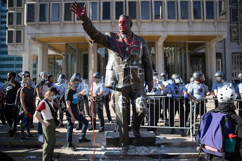 Police stand near the former mayor's vandalized statue on May 30 during protests over the death of George Floyd. (Photo: ASSOCIATED PRESS)